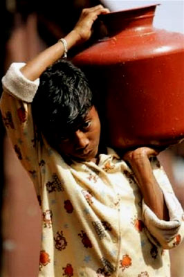 A boy carries water to his family