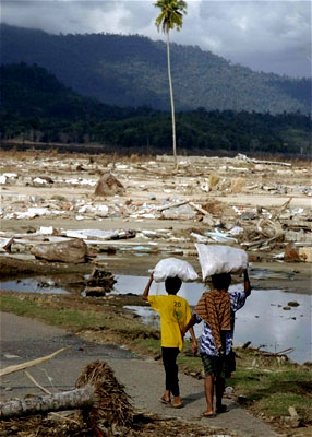 A woman and her son carry bags as they walk amid the destruction in sumatra