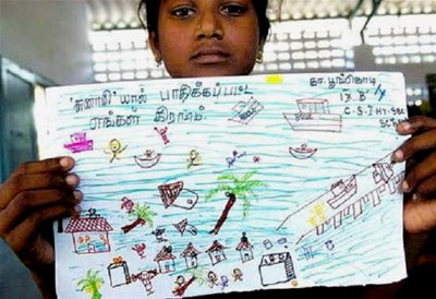 A young girl holds her drawing of the tsunami
