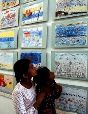 Two young girls view other children's drawings of the tsunami in Sri Lanka