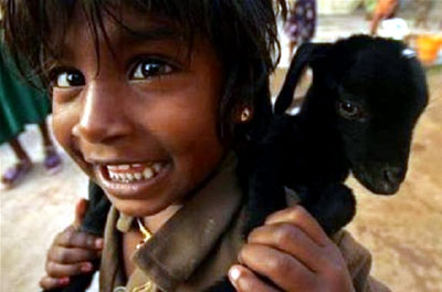 A young girl carries her baby goat on her back