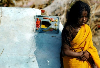 An intropective young girl stands amid the destruction in southern India