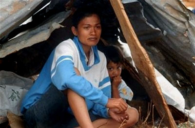 A woman and her son rest in their makeshift shelter