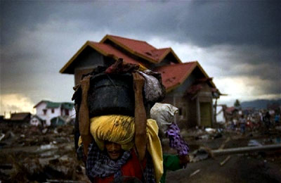 A man carries some of his personal items from his destroyed home in Banda Aceh, Indonesia