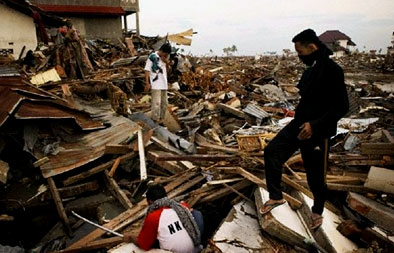 Men search for survivors amid the rubble of Banda Aceh, Indonesia