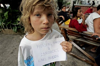 A young boy holds up a sign that reads: