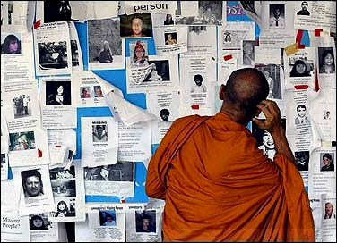 A buddhist monk views missing people notices