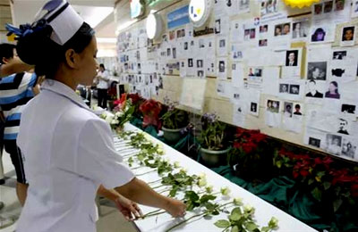A nurse places a rose in front of missing people notices