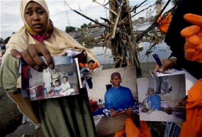 A woman shows a picture of her missing family members