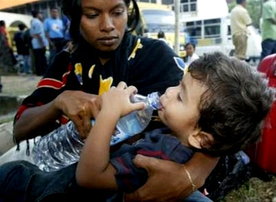 A mother gives water to her son