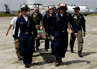 U.S. Navy personnel tranport an injured man