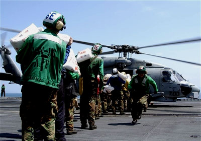 U.S. Navy personnel load bags of rice on a helicopter