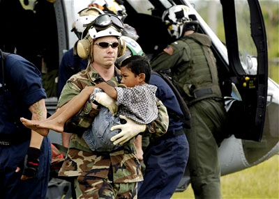A U.S. Navy man carries a wounded child from a transport helicopter