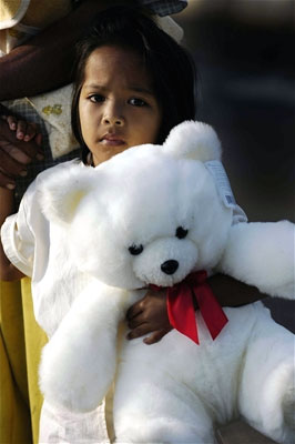 A young girl holds a teddy bear that a U.S. Navy man gave her
