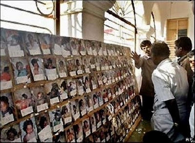 Relatives of missing people look at one of the numerous photo walls which show pictires of the dead