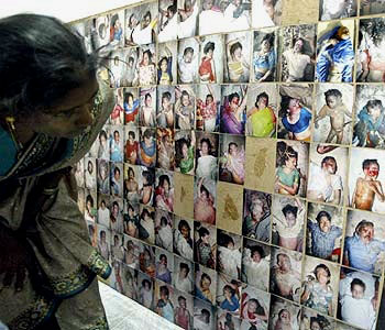 A woman searches for a relative among the pictures of those who passed away in the tsuanmi