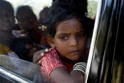 A sad young girl looks out a car window at the destruction in south India