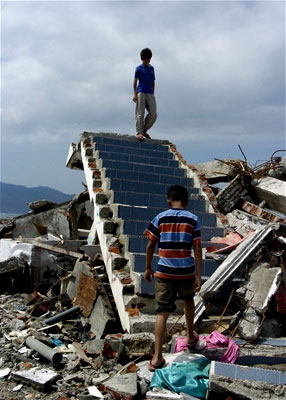 Stairs to nowhere -- Two boys walk on a staircase next to a destroyed building