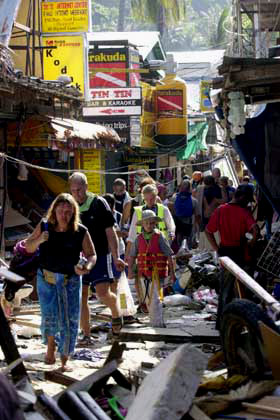 Tourists walk through rubble in Thailand.