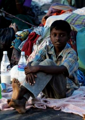 A boy rests after receiveing his water
