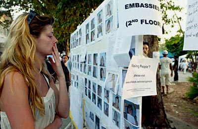 Tsunami Pictures: #6 - A woman views photos of missing people.