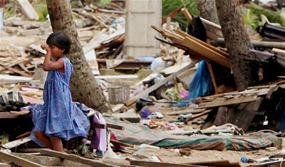 A young girl cries as she views her family's destroyed home